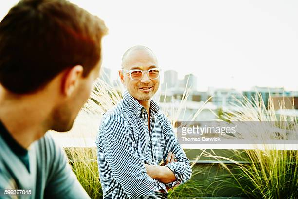 smiling businessman in discussion with colleague - checked pattern stock pictures, royalty-free photos & images