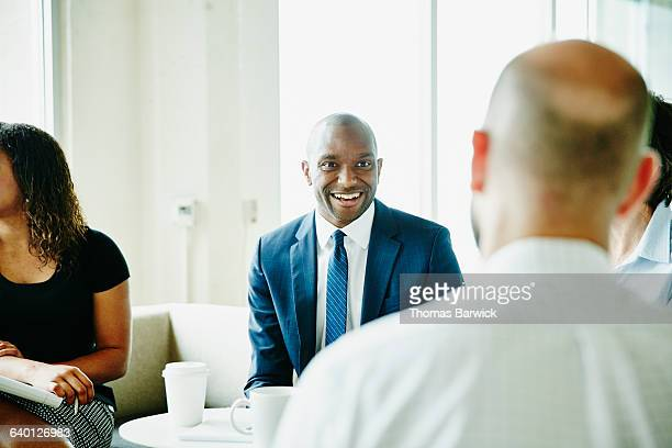 smiling businessman in discussion with colleagues - business finance and industry stock pictures, royalty-free photos & images