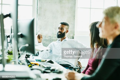 Smiling businessman in discussion with colleagues while sitting at workstation in high tech office