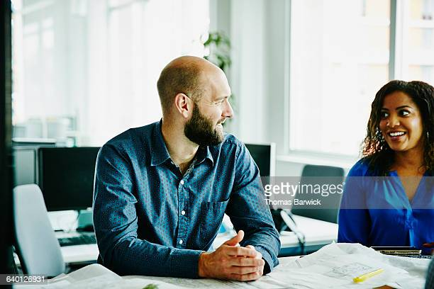 Smiling businessman in discussion with coworker