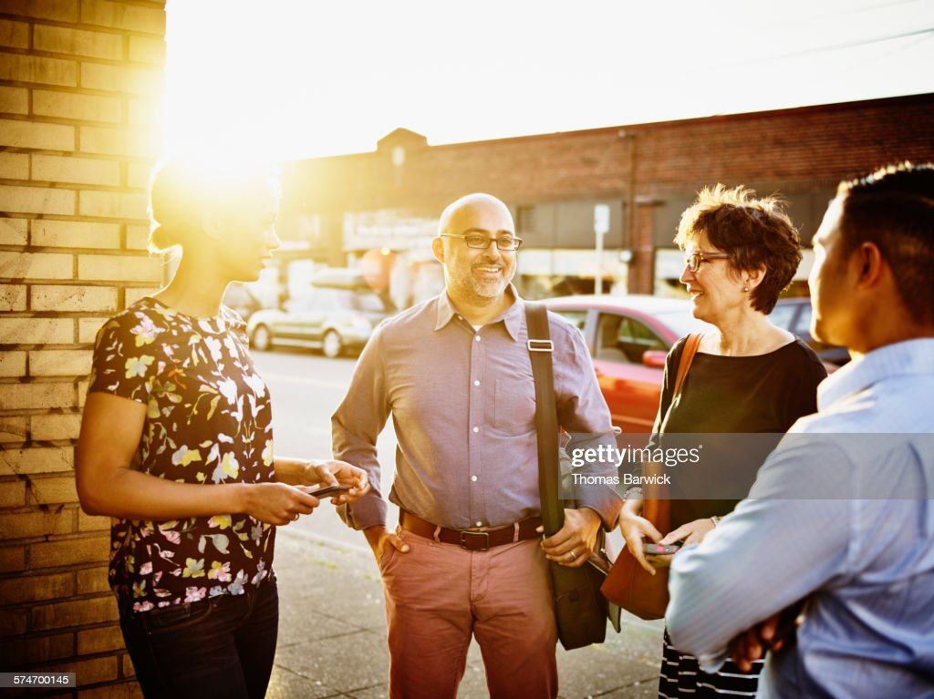 Smiling businessman in discussion with coworkers : Stock Photo
