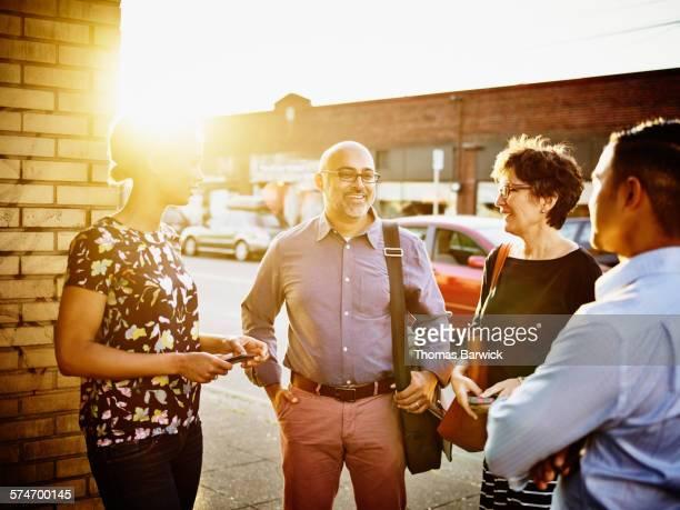 smiling businessman in discussion with coworkers - participacion ciudadana fotografías e imágenes de stock