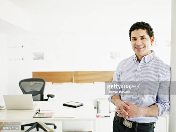 Smiling businessman in doorway of startup office