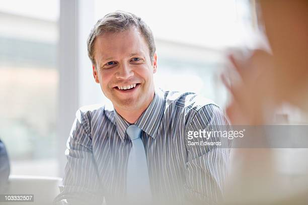 smiling businessman in meeting - incidental people stock pictures, royalty-free photos & images