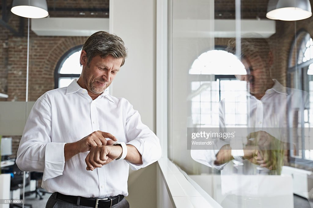 Smiling businessman in office looking at smartwatch : Stock Photo