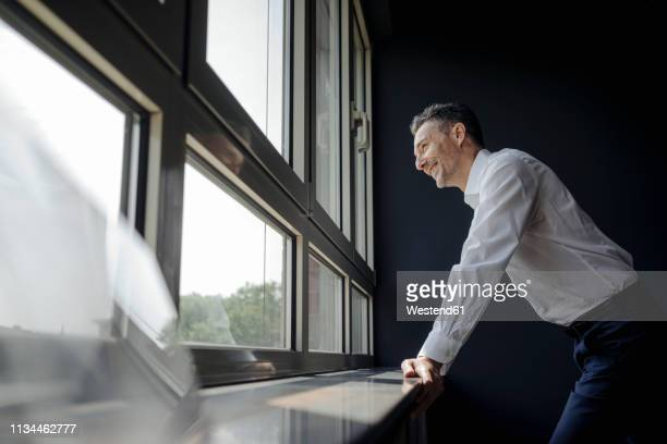 smiling businessman in office looking out of window - geschäftskleidung stock-fotos und bilder