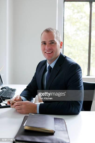 Smiling businessman in office, portrait