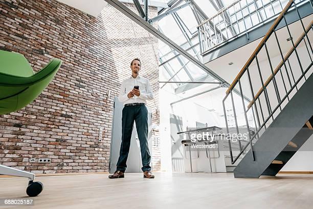 smiling businessman in office with cell phone - aufnahme von unten stock-fotos und bilder