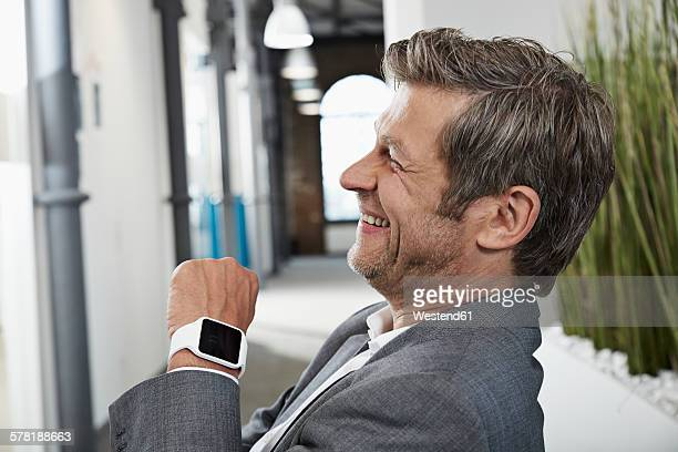 Smiling businessman in office with smartwatch