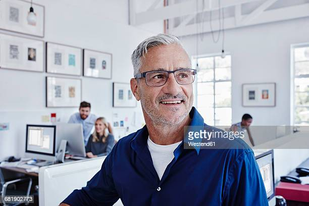 Smiling businessman in office with staff in background