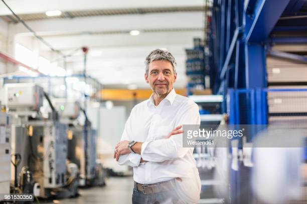 smiling businessman in production hall - one mature man only stock photos and pictures