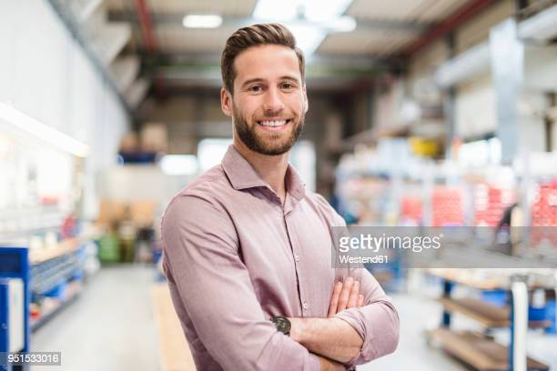 smiling businessman in production hall - finanzen und wirtschaft stock-fotos und bilder