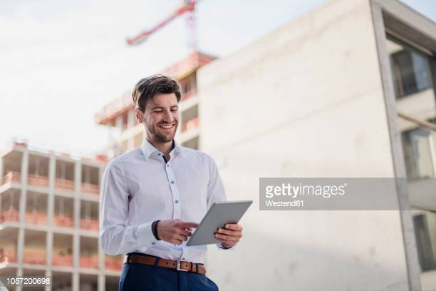 smiling businessman in the city using tablet - businesswear stock pictures, royalty-free photos & images