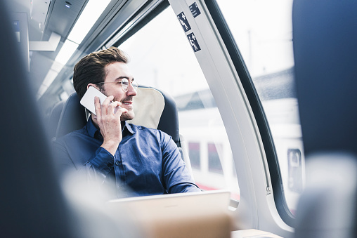 Smiling businessman in train on cell phone - gettyimageskorea
