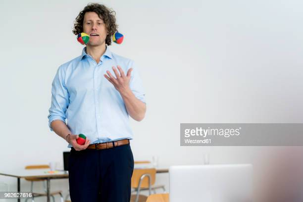 smiling businessman juggling balls in his office - juggling stock pictures, royalty-free photos & images