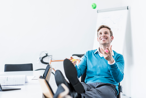 Smiling businessman juggling with balls in office - gettyimageskorea