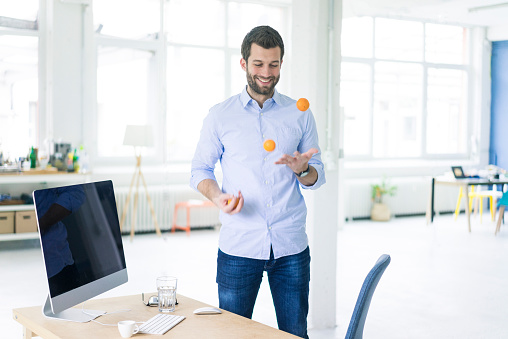 Smiling businessman juggling with tangerines in office - gettyimageskorea