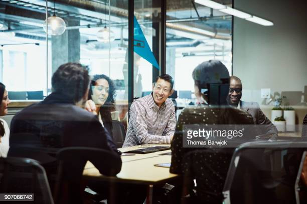 smiling businessman leading client meeting in office conference room - board room stock pictures, royalty-free photos & images