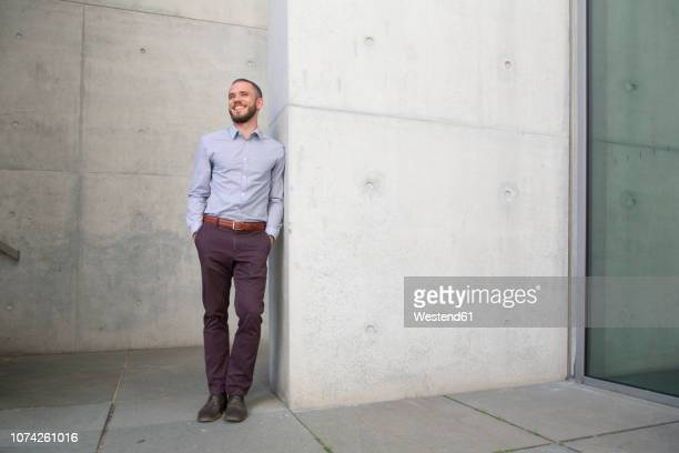smiling businessman leaning against a wall - lässige kleidung stock-fotos und bilder