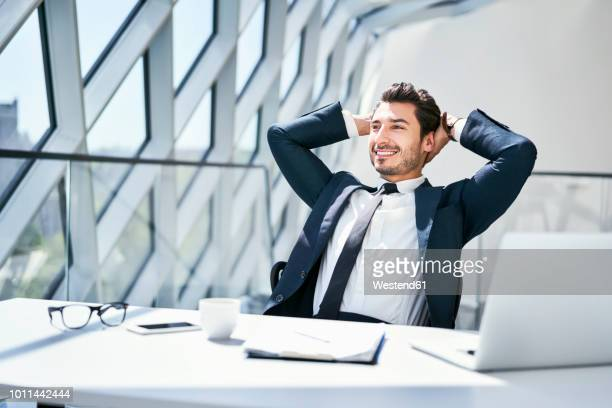smiling businessman leaning back at desk in modern office - hands behind head stock pictures, royalty-free photos & images