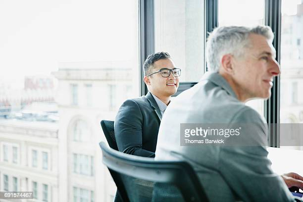 Smiling businessman listening during meeting