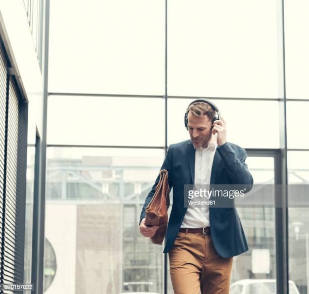 smiling businessman listening to music with headphones - sakko stock-fotos und bilder
