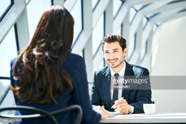 smiling businessman looking at businesswoman in modern office - job interview stock pictures, royalty-free photos & images