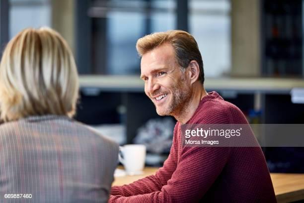 Sonriente hombre de negocios observando un colega en oficina