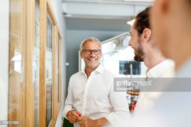 smiling businessman looking at colleagues in office - drei personen stock-fotos und bilder
