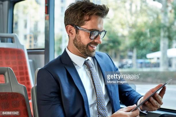 Empresario sonriente mirando la tableta digital