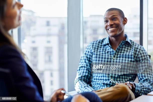 ビジネスマンのウィンドウに対して女性の同僚を見てにこにこしています。若い人の協力者は、創造的なオフィスの椅子に座っています。スマート カジュアルを着ています。