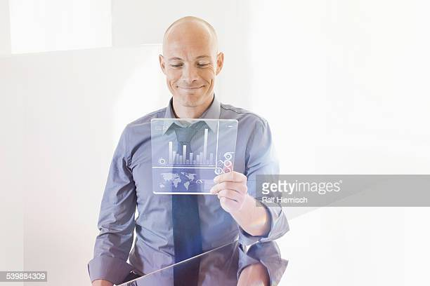 Smiling businessman looking at futuristic digital tablet at desk in office