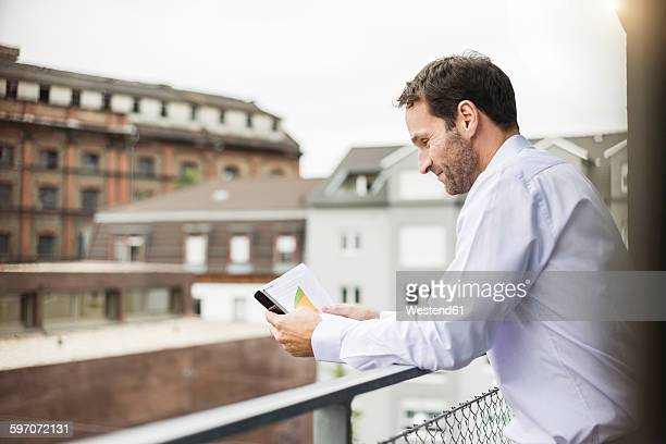 Smiling businessman looking at his smartphone