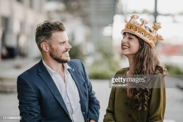 smiling businessman looking at woman wearing a crown - kopfbedeckung stock-fotos und bilder