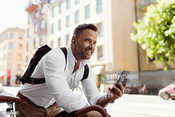 Smiling businessman looking away while holding smart phone on street