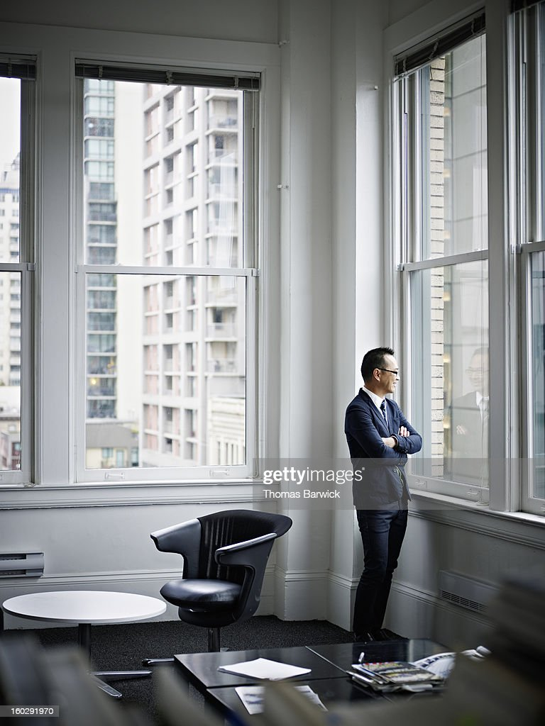 Smiling businessman looking out office window : Stock Photo