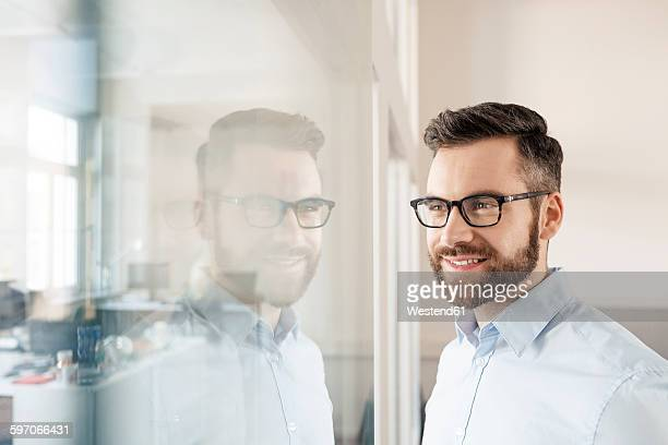 Smiling businessman looking through glass wall