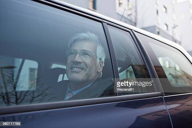 Smiling businessman looking through window of his car