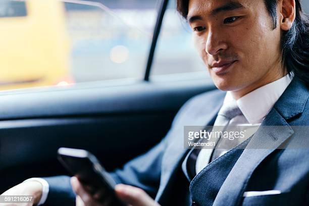 Smiling businessman on back seat of car using cell phone