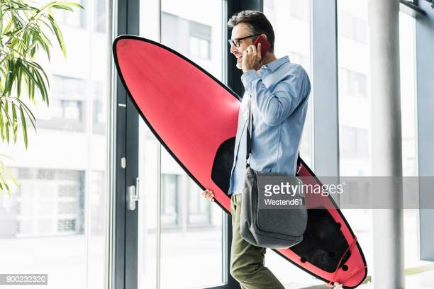smiling businessman on cell phone carrying surfboard - leisure equipment stock pictures, royalty-free photos & images
