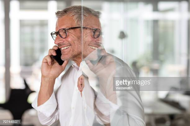 Smiling businessman on cell phone in office