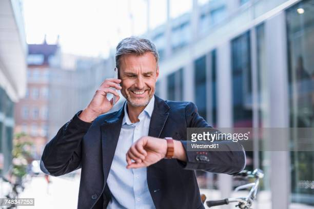 Smiling businessman on cell phone in the city checking the time