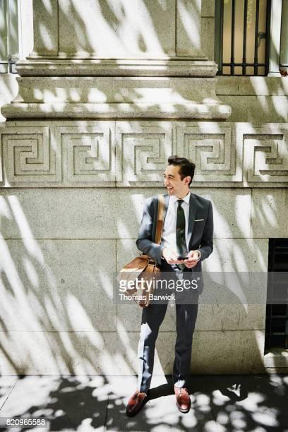 Smiling businessman on city sidewalk