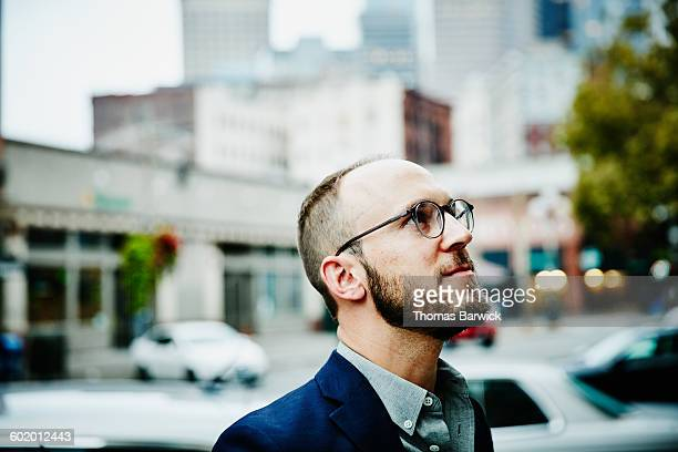 smiling businessman on city street looking up - receding hairline stock pictures, royalty-free photos & images