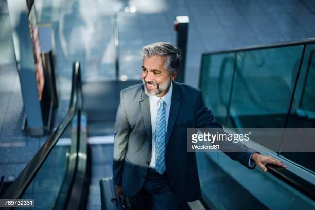 smiling businessman on escalator - 55 59 jahre stock-fotos und bilder