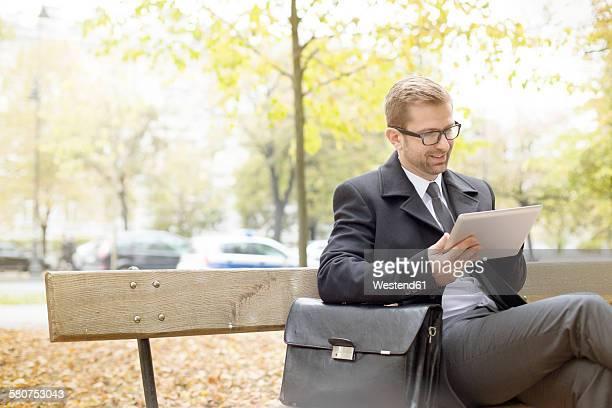 Smiling businessman on park bench using digital tablet