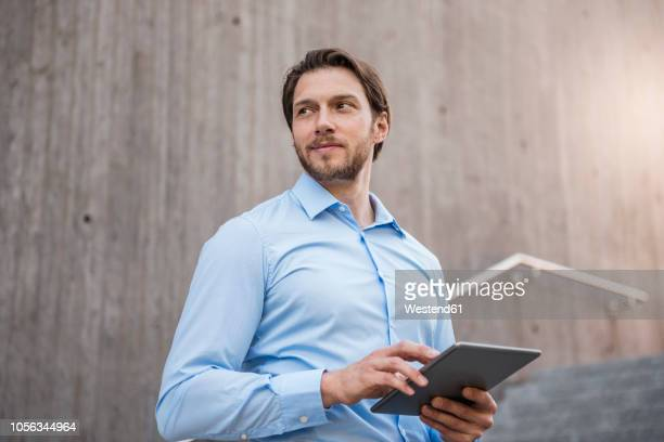 Smiling businessman on stairs with tablet looking sideways