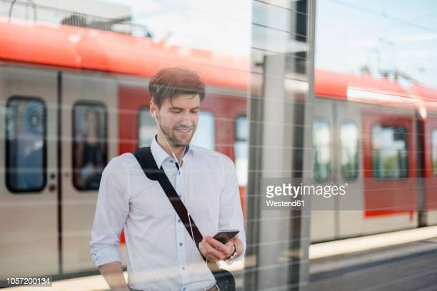 smiling businessman on station platform with earphones and cell phone - bahnhof stock-fotos und bilder