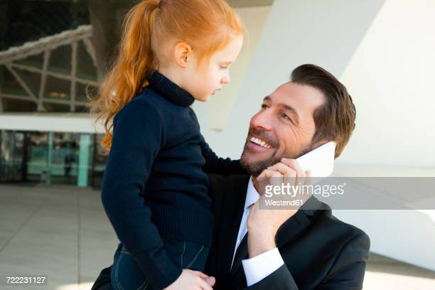 Smiling businessman on the phone holding daughter