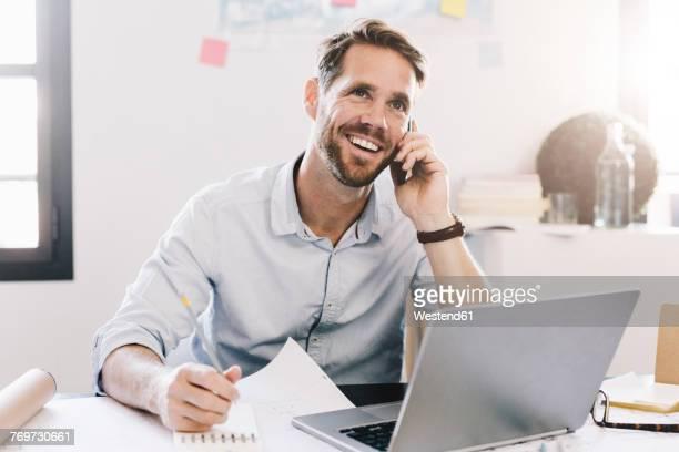 smiling businessman on the phone in his office - independência imagens e fotografias de stock